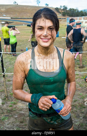 A smiling fit young 19 year old woman competitor at the finish of an 8km obstacle course challenge - Stock Image