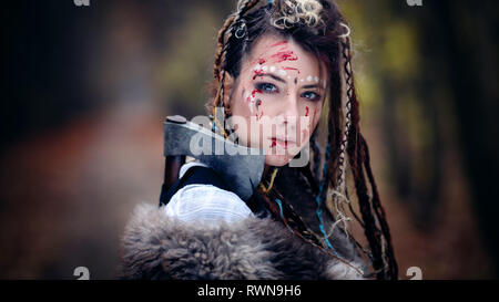 Warrior Beauty with trace of blood on her face. Viking Woman. Close-up portrait. Cinematic look - Stock Image