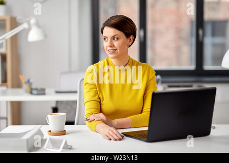 businesswoman with laptop computer at office - Stock Image