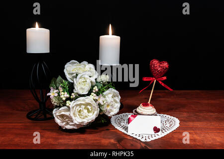 Beautiful bouquet of arranged flowers white candles, white heart shaped dillie with a cuocake and a pick with a heart on a holder on a wooden table. m - Stock Image