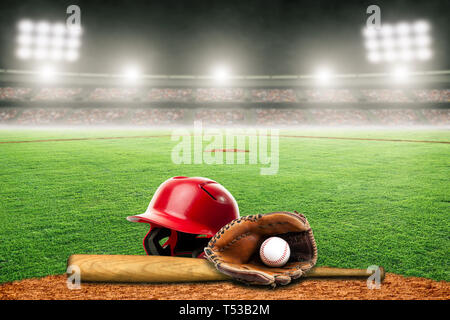 Baseball helmet, bat, glove and ball on field at brightly lit outdoor stadium. Focus on foreground and shallow depth of field on background and copy s - Stock Image