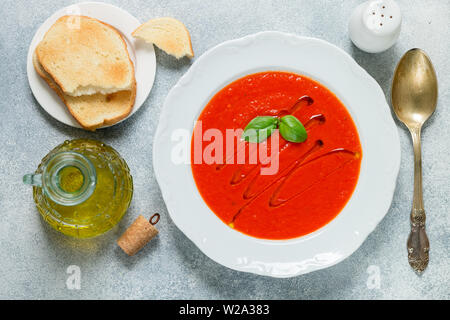 Tomato soup with Basil and spices in a white plate. A thick, hearty dish, served with bread toast and olive oil. Selective focus - Stock Image