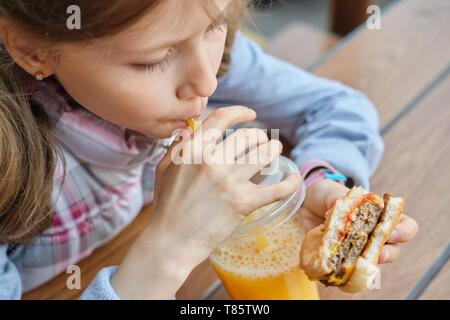 Closeup of hand of kid eating burger and drinking orange juice. - Stock Image