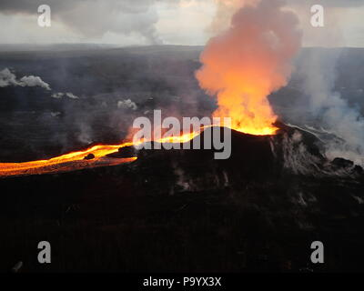 Lava and ash pour out from fissure 8 as a lava channel flows toward the ocean caused by the Kilauea volcano eruption July 14, 2018 in Hawaii. - Stock Image