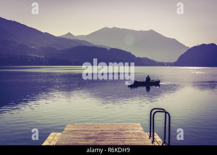 Early morning fishing at alpine lake in mountain valley. Instagram filter - Stock Image
