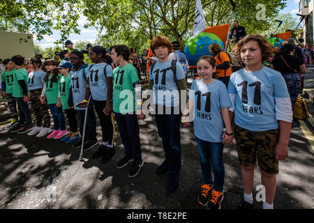 London, UK. 12th May 2019. 11-year-olds  hold hands in a line and prepare to lead several thousand mothers and children and some fathers from Hyde Park Corner to a rally filling Parliament Square, backing Extinction Rebellion's call for the drastic and urgent action needed to avert the worst consequences of climate change, including possible human extinction. Our politicians have declared a climate emergency but now need to take real action rather than continuing business as usual which is destroying life on our planet. Peter Marshall/Alamy Live News - Stock Image