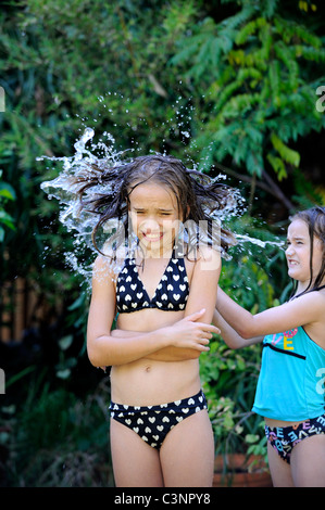 Child throwing bucket of water over her older sister. - Stock Image
