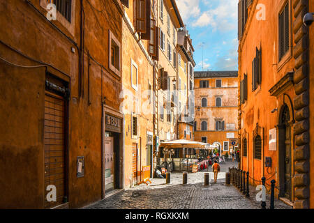 Rome, Italy - September 30 2018: A woman walks through an empty alley towards a sidewalk cafe and small piazza in the historic center of Rome, Italy - Stock Image