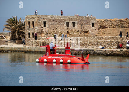 Chania, Crete, Greece. June 2019.  A small tourist submarine passing a long mole along the Old Venetian Harbour in Crete. - Stock Image