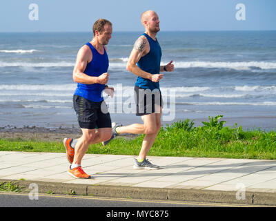 Two men jogging along a road on the North Yorkshire coast - Stock Image