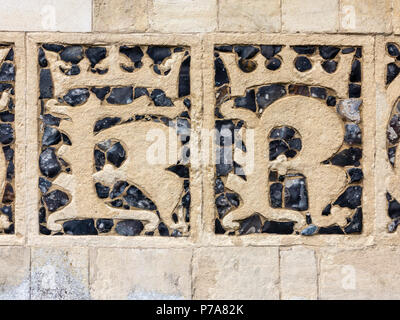 Knapped flint and stone Lombardic letterforms MS AH KR set into exterior wall of Holy Trinity Church Blythburgh  Suffolk England - Stock Image