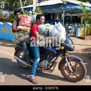People on a motorbike with shopping in India - Stock Image