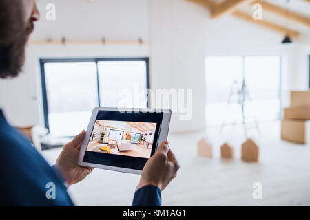 Midsection of man with tablet, looking at interior design sketches. A new home concept. - Stock Image
