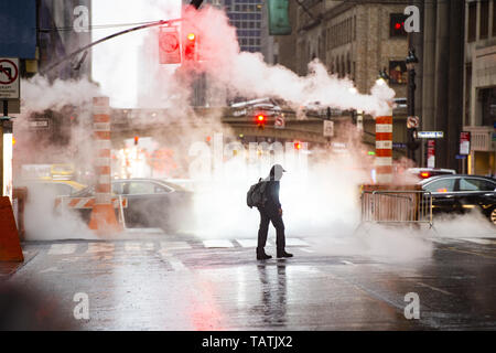 A black male is crossing the 42nd street in Manhattan while steam coming out from from the manholes. - Stock Image