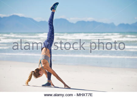 Woman Wearing Sportswear In Gymnastic Pose On Beach In South Africa - Stock Image