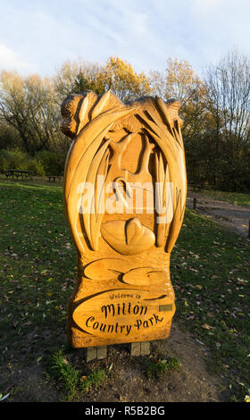 Milton Country Park carved wooden welcome sign side lit in setting sun - Stock Image