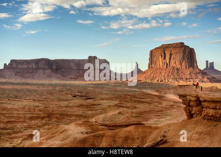 Evening at Monument Valley, Navajo Tribal park, Colorado, USA. Navajo horseman watching the trail form John Ford's - Stock Image
