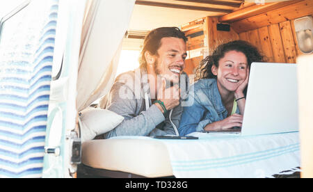 Happy couple watching videos on their computer inside minivan at sunset - Travel couple using laptop during their journey on a vintage mini van - Stock Image