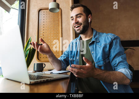 Photo of handsome caucasian man wearing denim shirt using earpod and laptop while working in cafe indoors - Stock Image