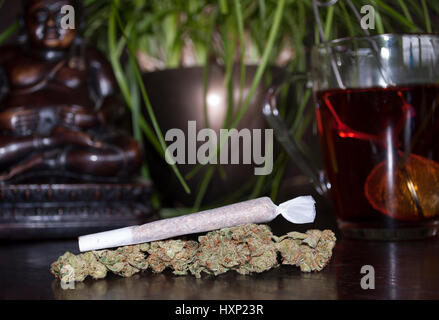 closeup of rolled marijuana weed joint and buds on wooden background, with Buddha statuette and cup of rooibos tea - Stock Image