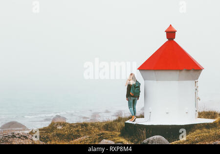 Traveler woman near lighthouse enjoying foggy sea view solo traveling lifestyle journey adventure outdoor solitude emotions - Stock Image