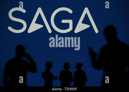 The Saga Insurance logo is seen on an LED screen in the background while a silhouetted person uses a smartphone in the foreground (Editorial use only) - Stock Image
