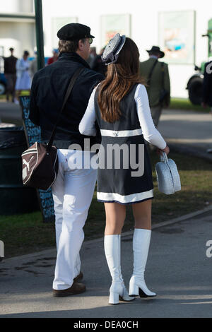 Chichester, West Sussex, UK. 14th Sep, 2013. Goodwood Revival. Goodwood Racing Circuit, West Sussex - Saturday 14th September. A couple walk into the circuit. Dressed in 60s clothing the lady has a black and white mini-dress and knee high white boots. Credit:  MeonStock/Alamy Live News - Stock Image