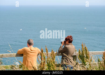 Woman female with binoculars bird watching at a viewpoint at Bempton Cliffs RSPB Reserve, UK. A male companion man is at her side. - Stock Image