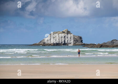 A holidaymaker standing in the sea at Crantock Beach looking out to The Goose uninhabited island off East Pentire Headland in Newquay in Cornwall. - Stock Image