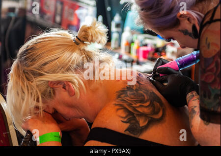 Skibbereen, West Cork, Ireland. 20th Oct, 2018. A customer finds it difficult to take the pain whilst having a tattoo done at the show. The show has been attended by many tattooists from across Ireland and the North. The event finishes tomorrow. Credit: Andy Gibson/Alamy Live News. - Stock Image