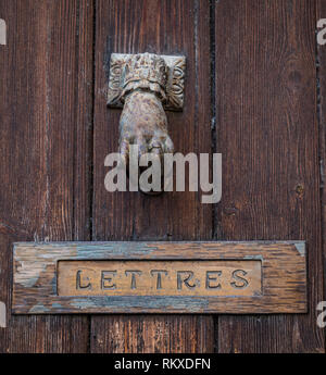 Hand door knocker and letter box in the village of Lourmains, France - Stock Image