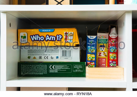 Poznan, Poland - November 18, 2018: Variation of child card and board games on white book shelves in a child room. - Stock Image