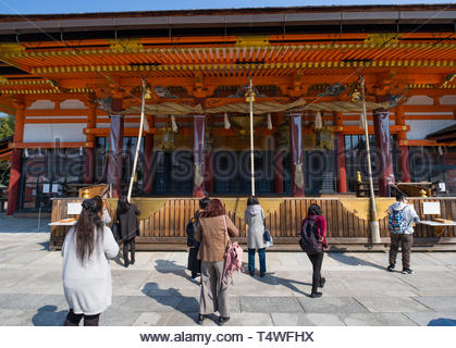 Woman ringing large Suzu bells hanging under the eaves of Yasaka Shrine Haiden, Gionmachi Kitagawa, Higashiyama-ku, Kyoto, Honshu, Japan - Stock Image