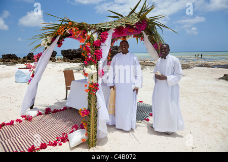 Zanzibar, Matemwe. Priests wait patiently for the bride and groom to arrive for a beach wedding. - Stock Image