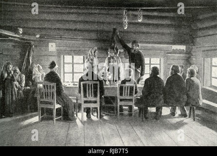 Peasants at a wedding feast, Finland -- one of the customs is for the bridegroom to lift the veil from the face of the bride. - Stock Image