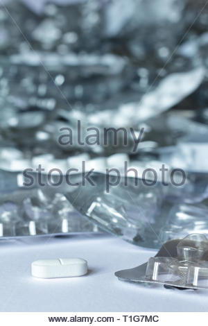 One single tablet in front of many empty blister packages on white background, drug misuse concept - Stock Image