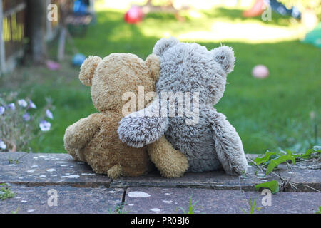 Back view of two teddy bears with their arms around each other, sitting on a step, looking at the garden. - Stock Image