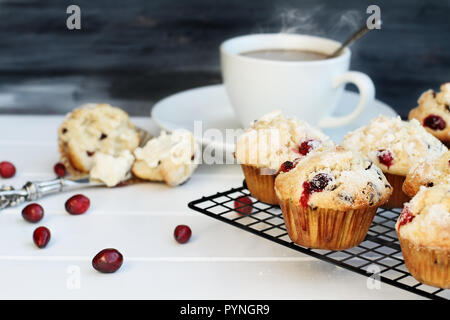 Cranberry Muffins cooling on a bakers rack with extreme shallow depth of field and open muffin with butter and a steaming hot cup of coffee in the bac - Stock Image