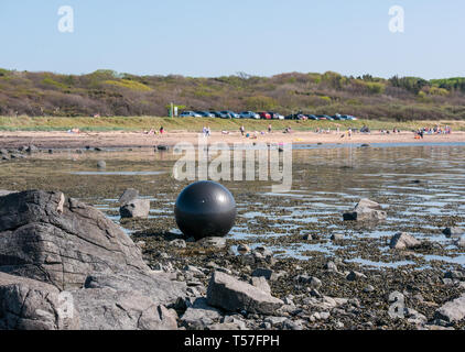 Longniddry Bents, East Lothian, Scotland, United Kingdom, 22nd April 20-19. UK Weather: a very warm sunny day with clear blue sky brings people out to enjoy the beach with a lost ball in the sea - Stock Image