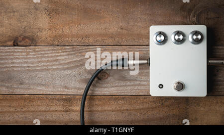 Blank white guitar pedal with vintage knobs and plugged jacks on wooden floor - Stock Image