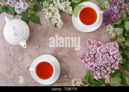 Tea set and flower decor on a textural background. Textural background with flowers and tea pair and place under the text. View from above. Flat lay.  - Stock Image