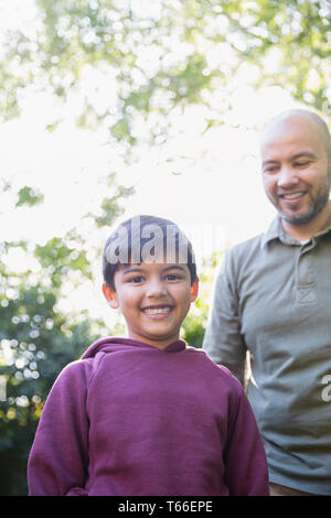 Portrait happy father and son in park - Stock Image