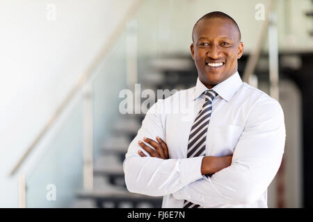 successful African office worker with arms crossed - Stock Image