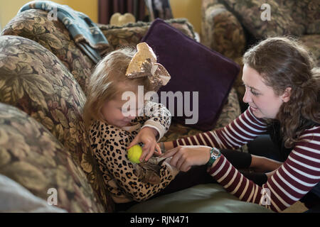 A 3 year old Caucasian girl cuddles and plays with a kitten and a ball while an adult woman looks on. - Stock Image