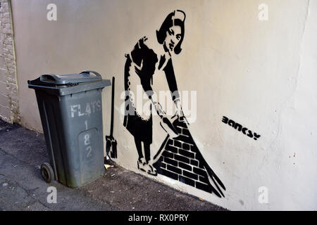 Stencil painting on wall of woman with dustpan with real rubbish bin next to painting, Question if Bansky - Stock Image