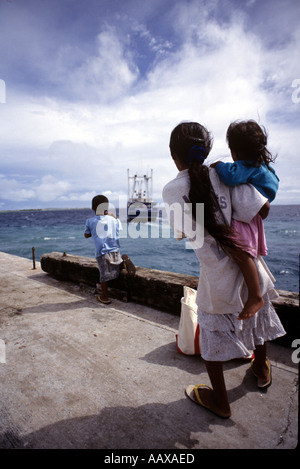 kids seeing off the local supply boat on the outer islands of the Marshall Islands - Stock Image