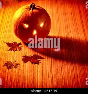 Stylish Halloween decoration, carved pumpkin with scary face and candlelight, dry tree leaves on a wooden table - Stock Image
