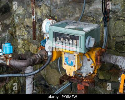 Old fuel pump meter, gauge and pipework on Elgol Pier on the isle of Skye, Scotland, UK - Stock Image