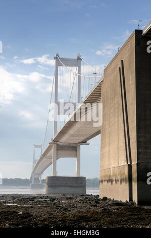 The older original Severn suspension bridge spanning the Severn estuary at low tide on a sunny day - Stock Image