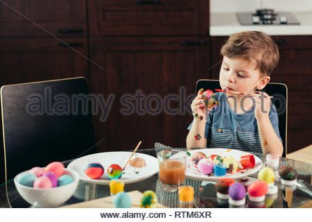 4-year old caucasian boy helps his mother with preparations to Easter. Concentrated kid is engaged in creative activity, painting out Easter eggs. chi - Stock Image